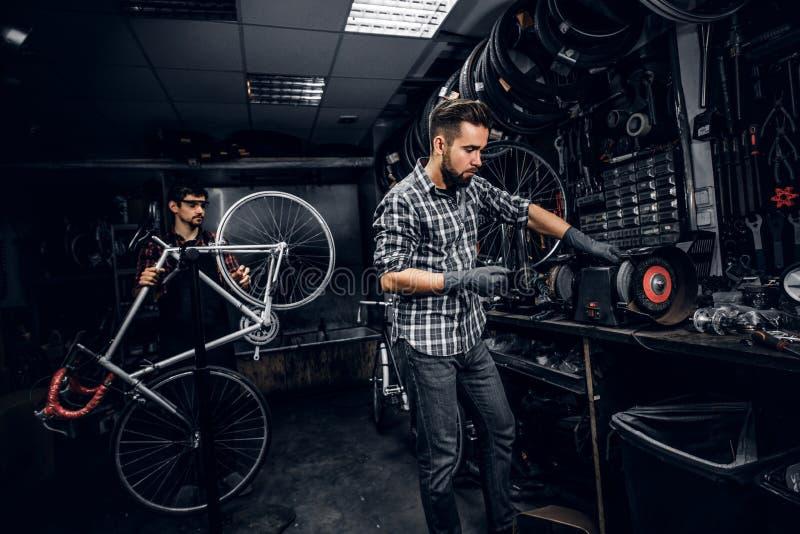 Den attraktiva mannen arbetar med maskinen på det upptagna cykelseminariet royaltyfri foto