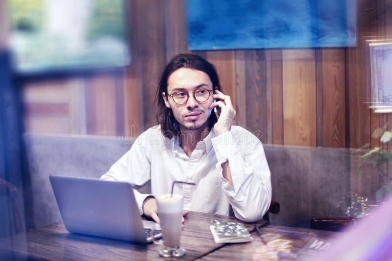 Den attraktiva mannen i den vita skjortan som talar vid telefonen och arbete på bärbara datorn i kafé eller restaurang och att ha fotografering för bildbyråer