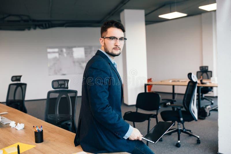 Den attraktiva mannen i glassess sitter på tabellen nära arbetsplatsen i regeringsställning Han bär den blåa skjortan, mörkt omsl fotografering för bildbyråer