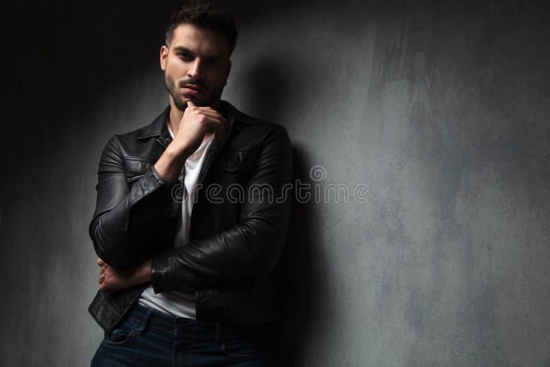 Den attraktiva mannen i piskar omslaget med fingret på hans haka royaltyfri foto