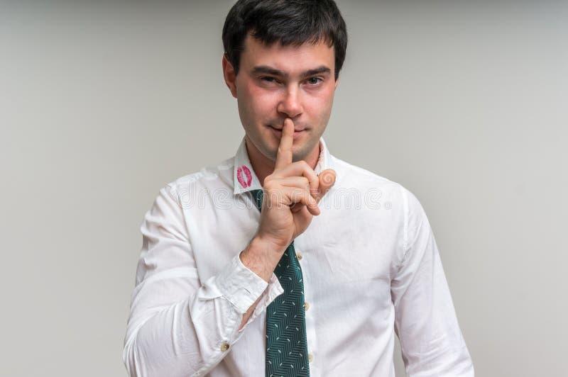 Den attraktiva mannen med fingret på kanter och läppstift på skjortan förser med krage arkivfoto