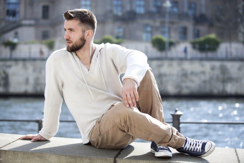 Den attraktiva mannen sitter på en vägg i berlin royaltyfri fotografi