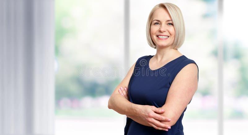 Den attraktiva mitt åldrades kvinnan med ett härligt leende nära fönstret arkivbilder
