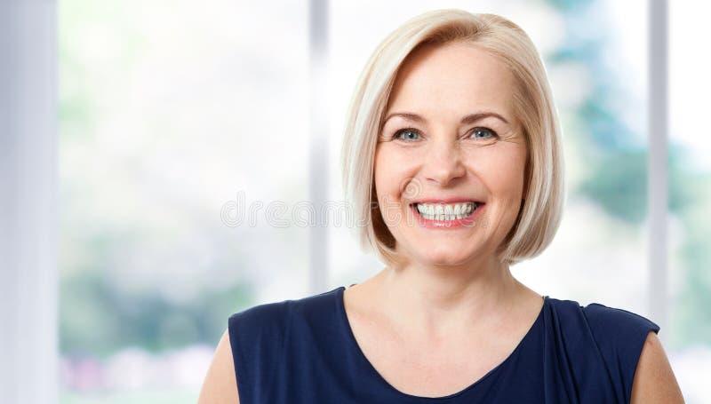 Den attraktiva mitt åldrades kvinnan med ett härligt leende nära fönstret arkivfoton