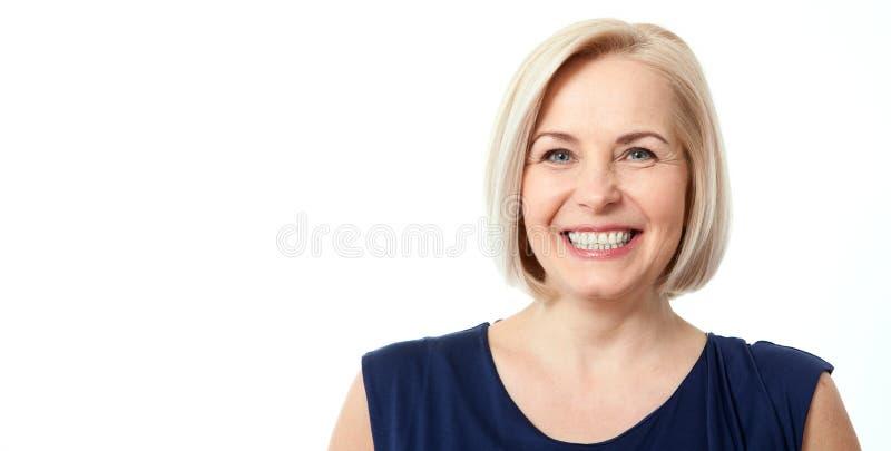 Den attraktiva mitt åldrades kvinnan med härligt leende på vit bakgrund arkivbild