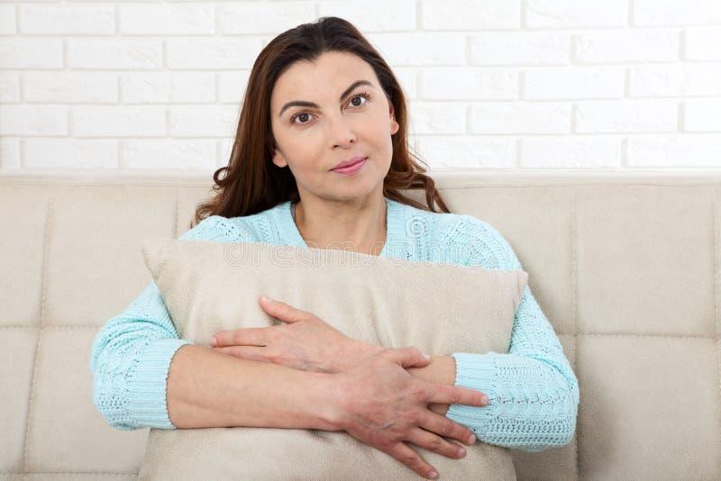 Den attraktiva mitt åldrades kvinnan som in camera ser koppla av hemma Det härliga framsidaslutet upp royaltyfri bild