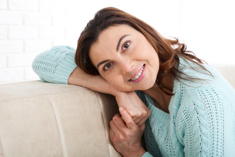 Den attraktiva mitt åldrades kvinnan som in camera ser koppla av hemma Det härliga framsidaslutet upp arkivfoto