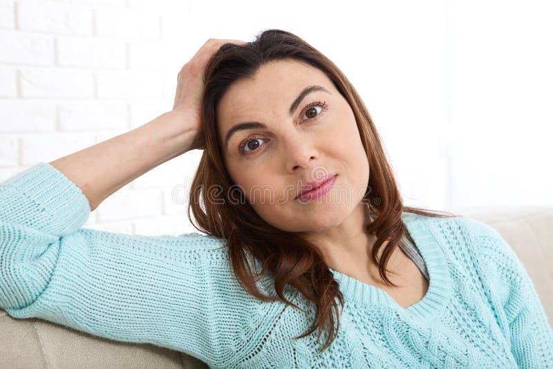 Den attraktiva mitt åldrades kvinnan som in camera ser koppla av hemma Det härliga framsidaslutet upp arkivbilder