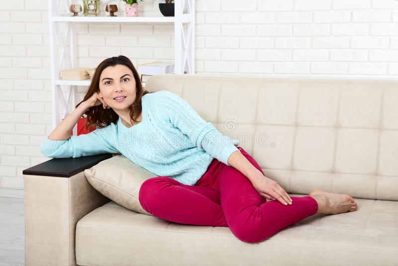 Den attraktiva mitt åldrades kvinnan som in camera ser koppla av hemma Det härliga framsidaslutet upp royaltyfria bilder