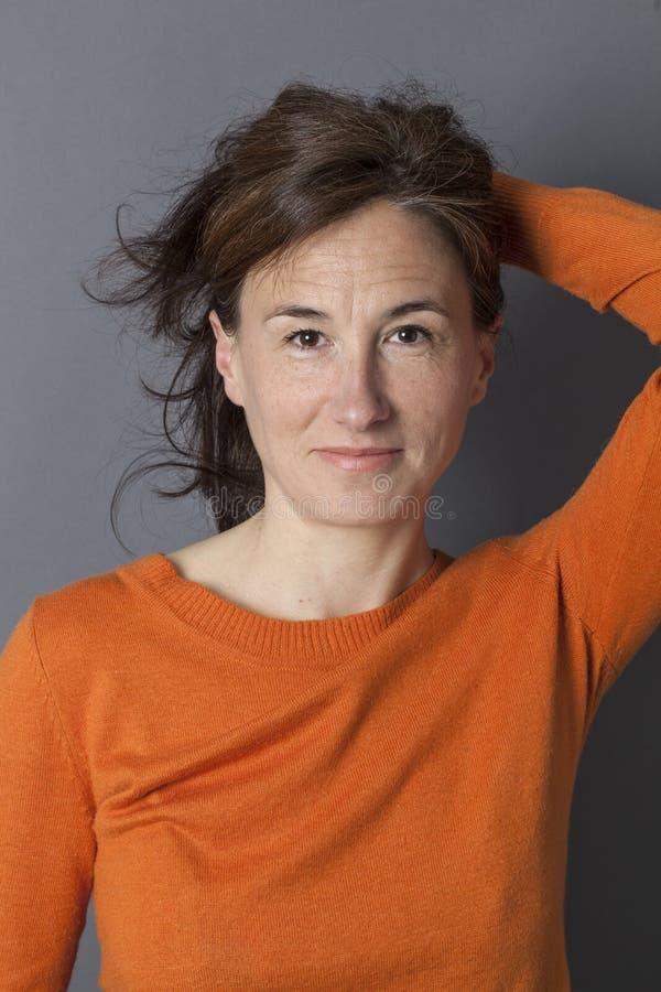 Den attraktiva mitt åldrades kvinnan som rymmer hennes sexiga långa bruna hår royaltyfri fotografi