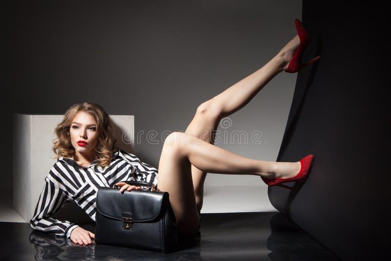 Den attraktiva modellen som ligger med kala ben i röda häl, och svart mode hänger löst royaltyfri bild