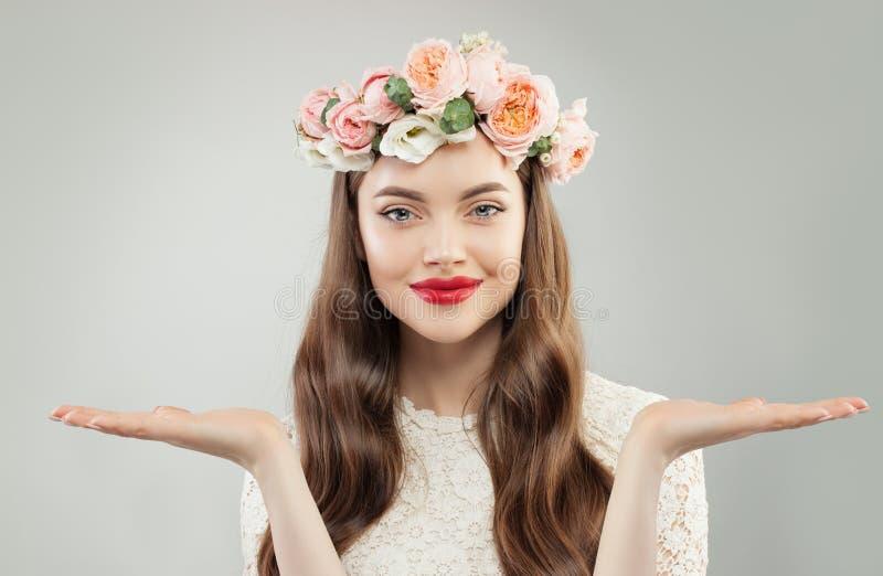 Den attraktiva modellen Woman Showing Two tömmer öppna händer på vit bakgrund Klar hud, lockigt hår, makeup och blommor arkivfoto