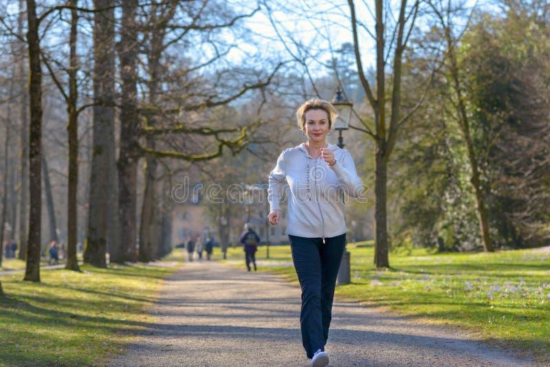 Den attraktiva mogna kvinnan som tar hennes dagstidning, joggar royaltyfri foto