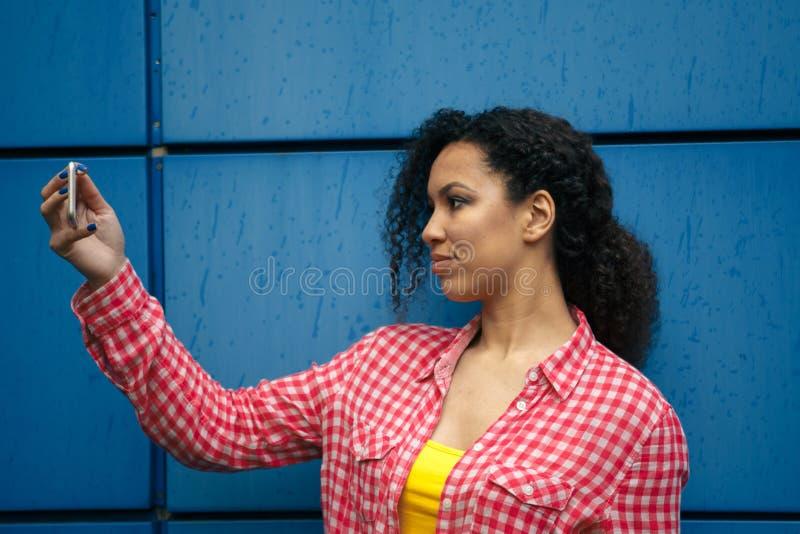 Den attraktiva mulattkvinnlign håller ögonen på videoen på hennes mobiltelefon, medan sitta i en coffee shop Hipsterflickan talar arkivfoton
