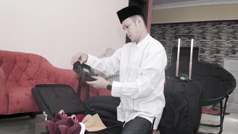 Den attraktiva muslim asiatiska mannen f?rbereder bagageresv?skan royaltyfri fotografi
