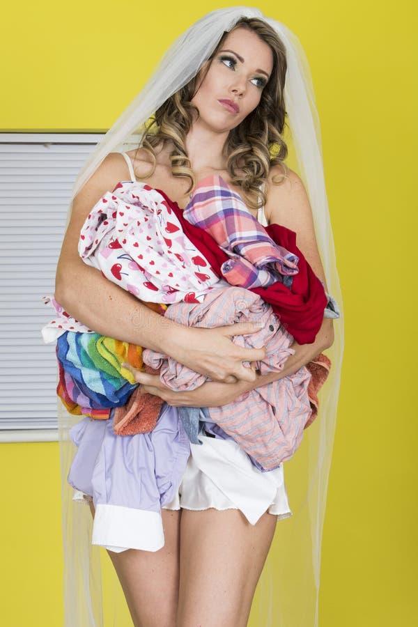 Den attraktiva oberörda unga kvinnan i bröllop skyler den olyckliga smutsiga tvätterit för innehavet arkivfoton