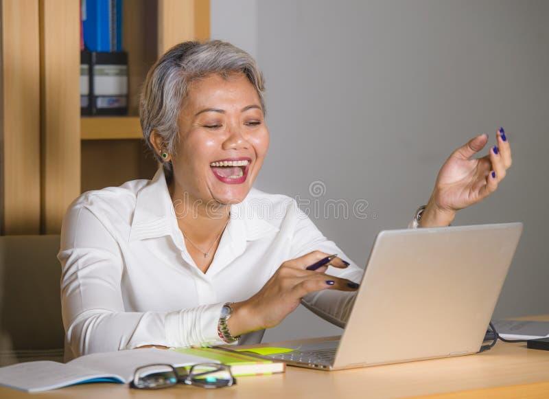 Den attraktiva och lyckliga lyckade mitt ?ldrades den asiatiska kvinnan f?r aff?ren som arbetar p? att le f?r skrivbord f?r b?rba fotografering för bildbyråer