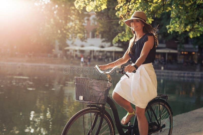 Den attraktiva ridningcykeln för den unga kvinnan längs ett damm i stad parkerar royaltyfri bild