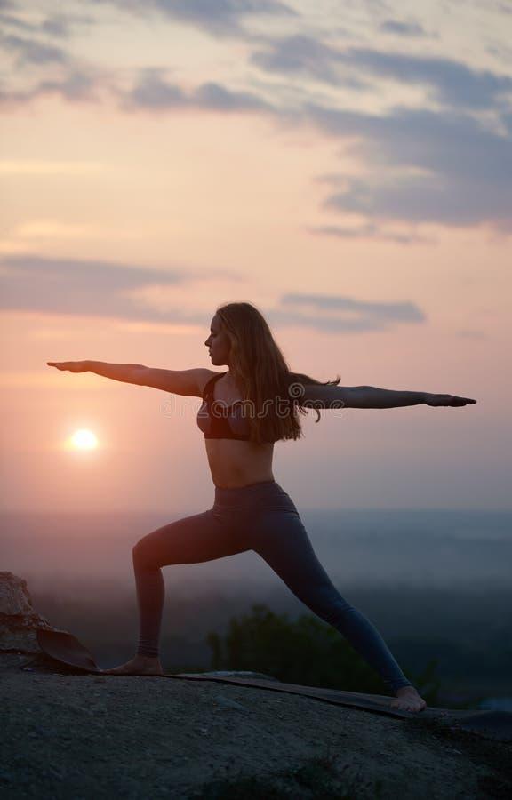 Den attraktiva slanka unga kvinnan som gör yoga, övar utomhus på bakgrund av härlig himmel arkivfoto