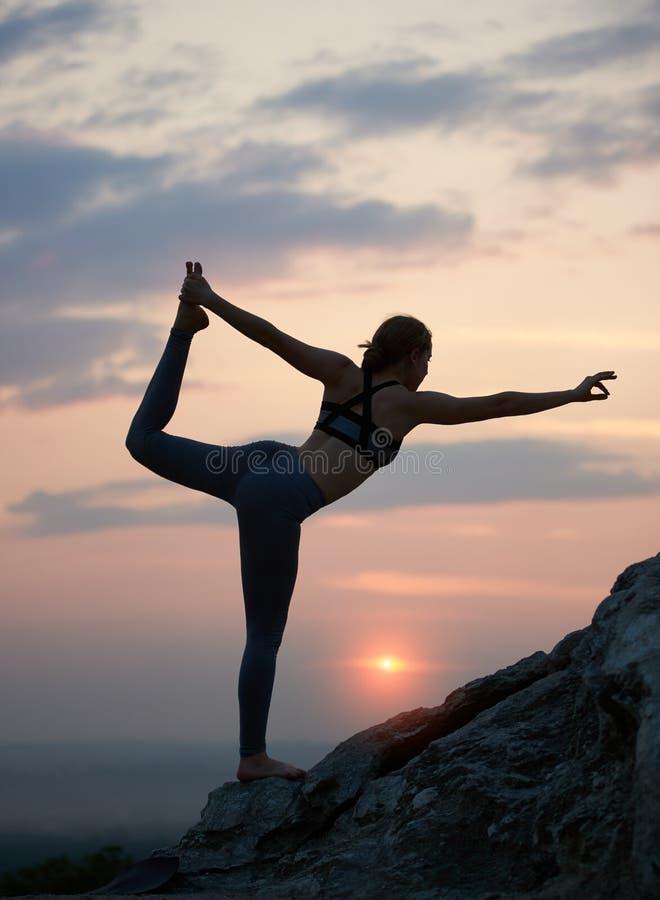 Den attraktiva slanka unga kvinnan som gör yoga, övar utomhus på bakgrund av härlig himmel royaltyfri foto
