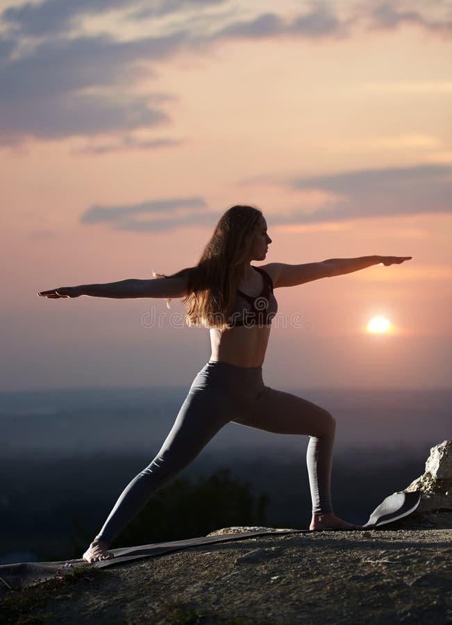 Den attraktiva slanka unga kvinnan som gör yoga, övar utomhus på bakgrund av härlig himmel royaltyfri bild