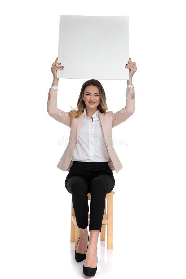 Den attraktiva smarta tillfälliga kvinnan rymmer det vita brädet i luften arkivbild