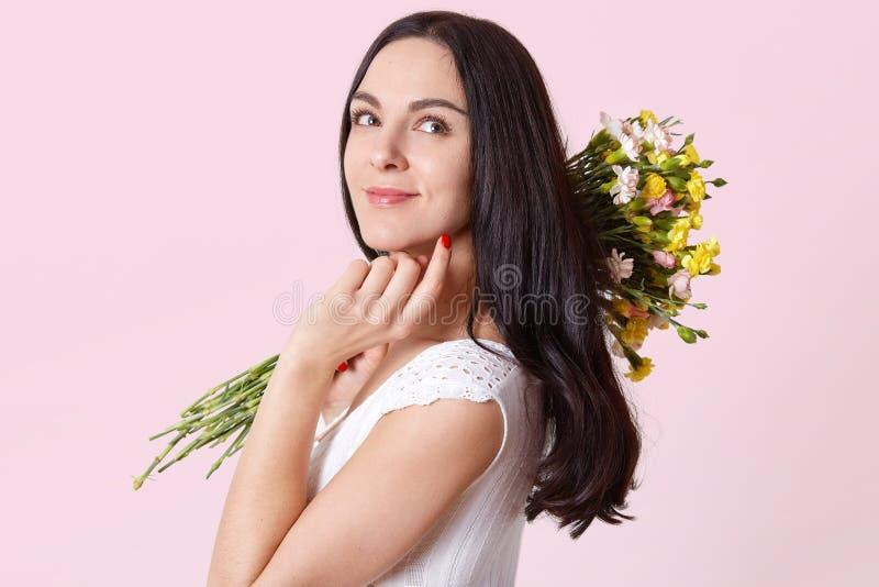 Den attraktiva spensliga unga damen rymmer blommor på hennes skuldra, trycker på hakan med fingrar och att stå sidewards som s royaltyfri bild