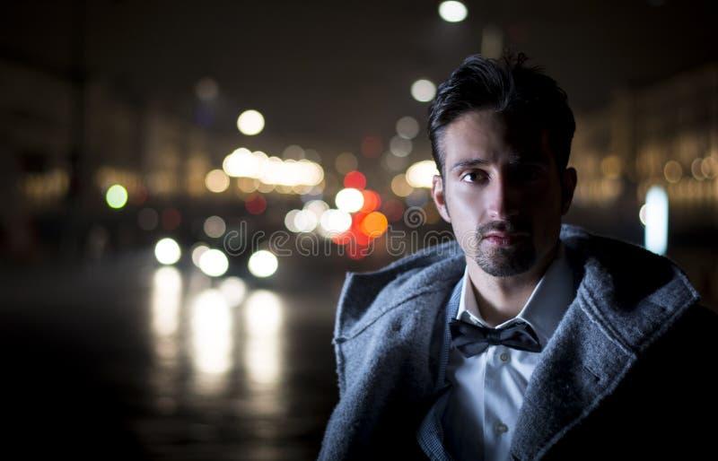 Den attraktiva ståenden för den unga mannen på natten med staden tänder bak honom arkivbilder