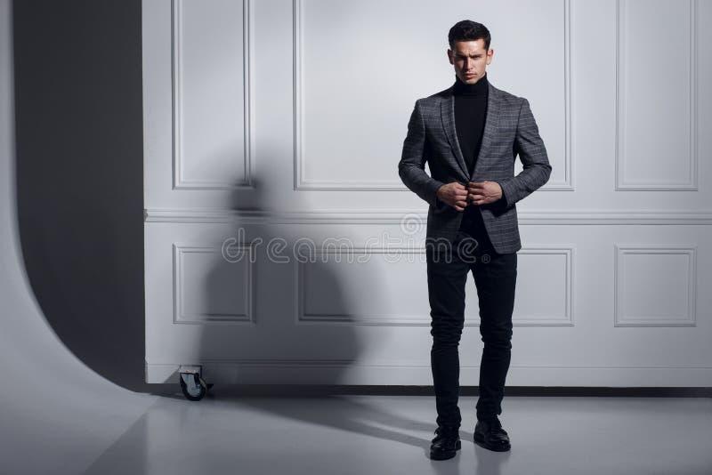 Den attraktiva, starka muskulösa unga mannen klä upp sig dräkten som poserar i studion som står nära väggen, skuggabakgrund arkivbilder