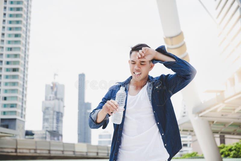Den attraktiva stiliga asiatiska mannen får törstig på grund av varm weathe royaltyfri fotografi
