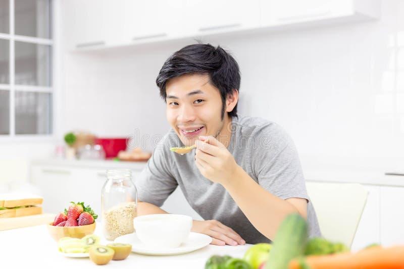 Den attraktiva stiliga mannen äter frukosten, eller sädesslag, frukter, mjölkar på arkivbilder
