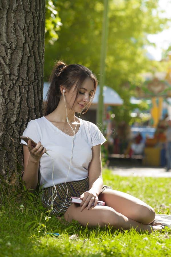 Den attraktiva studentflickan parkerar in det fria royaltyfria foton
