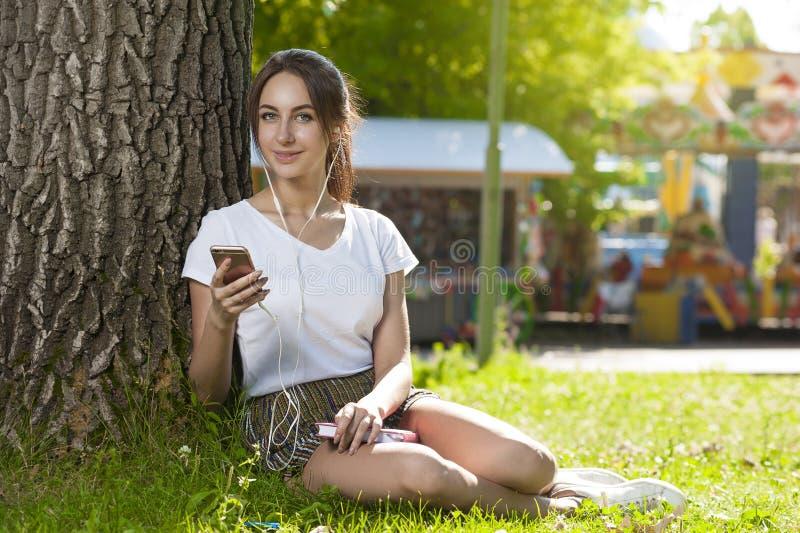 Den attraktiva studentflickan parkerar in det fria arkivfoto