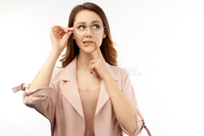 Den attraktiva unga affärskvinnan ser pensively uppåt, bär anblickar, tomt kopieringsutrymme för annonsering arkivbilder