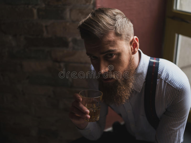 Den attraktiva unga affärsmannen tycker om alkoholdrinken royaltyfria foton