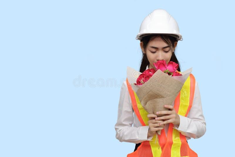 Den attraktiva unga asiatiska kvinnateknikern som rymmer en bukett av röda rosor på blått, isolerade bakgrund royaltyfri bild