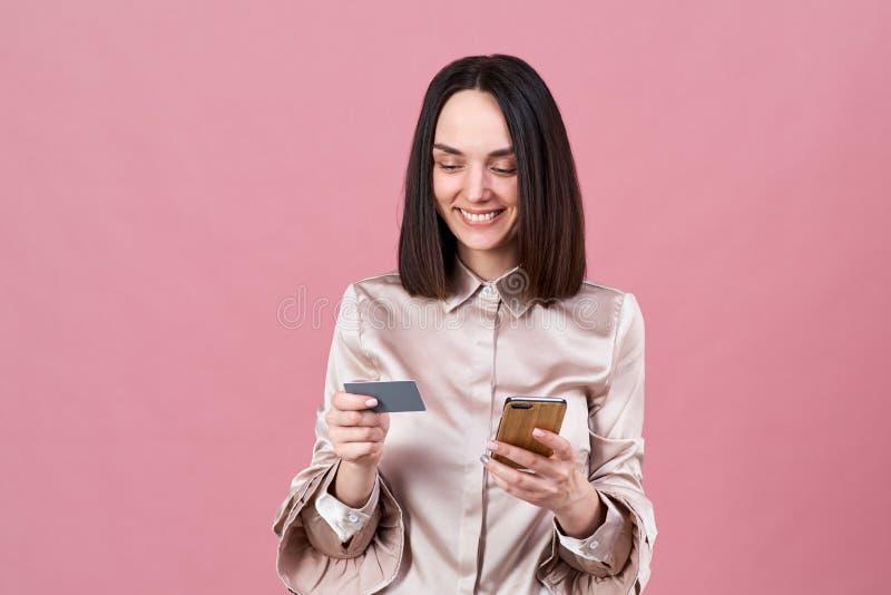 Den attraktiva unga brunettkvinnan i en stilfull blus gör online-köp och använder en telefon och en kontokort royaltyfri fotografi