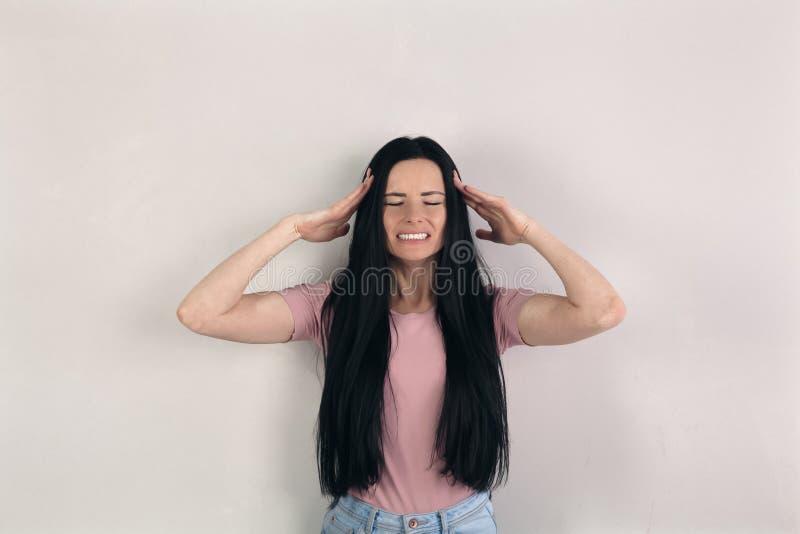 Den attraktiva unga brunettkvinnan med långt hår står av den gråa bakgrunden som har stark huvudvärk och rymmer händer vid arkivfoto