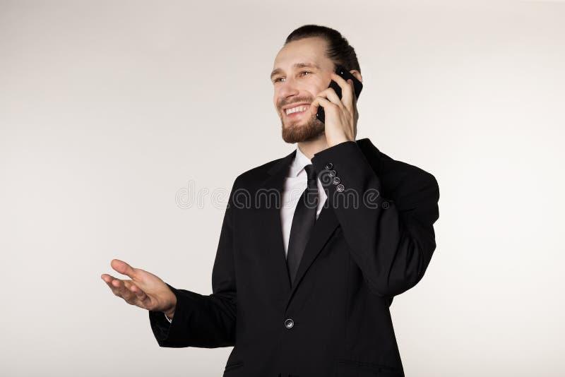 Den attraktiva unga busibessmanen i svart dräktsmilig och samtal på telefonen med lyftt gömma i handflatan arkivbild