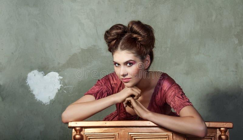 Den attraktiva unga damen i rosa färger klär och roligt utforma posera på fotografering för bildbyråer