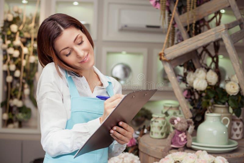 Den attraktiva unga försäljaren mottar en beställning arkivbilder