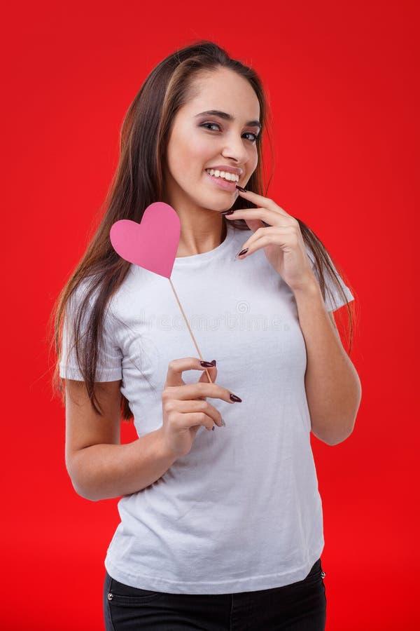 Den attraktiva unga flickan, gulligt le och att rymma en liten rosa färg skyler över brister hjärta på en pinne royaltyfri fotografi