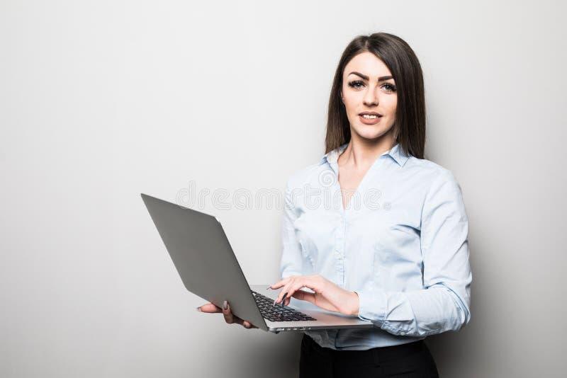Den attraktiva unga flickan i tillfällig kläder rymmer en bärbar dator, ser kameran och ler, på grå bakgrund arkivfoto