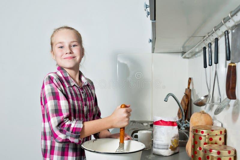 Den attraktiva unga flickan lagar mat på kök Framställning av kakor och av kakor royaltyfria foton