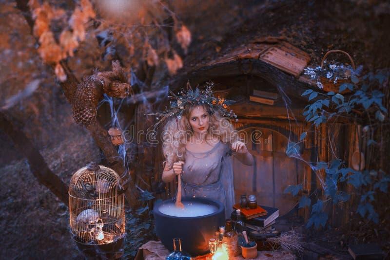 Den attraktiva unga flickan med blont hår med en fantastisk frodig krans på hennes huvud i skogen förbereder ett stort fotografering för bildbyråer