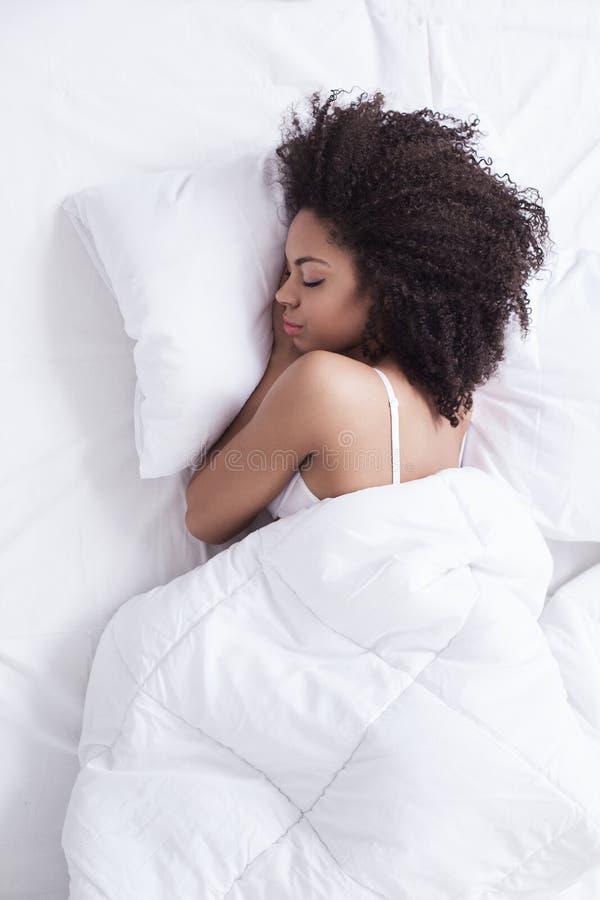 Den attraktiva unga flickan sover hemma royaltyfri foto