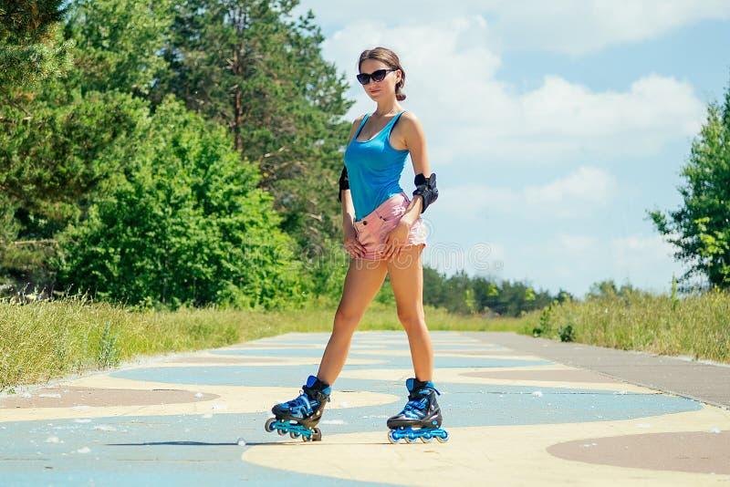 Den attraktiva unga friska, smala brunettsexiga kvinnan i kortrosa shorts och blå topp med skyddsarmbågarna och knä royaltyfria foton