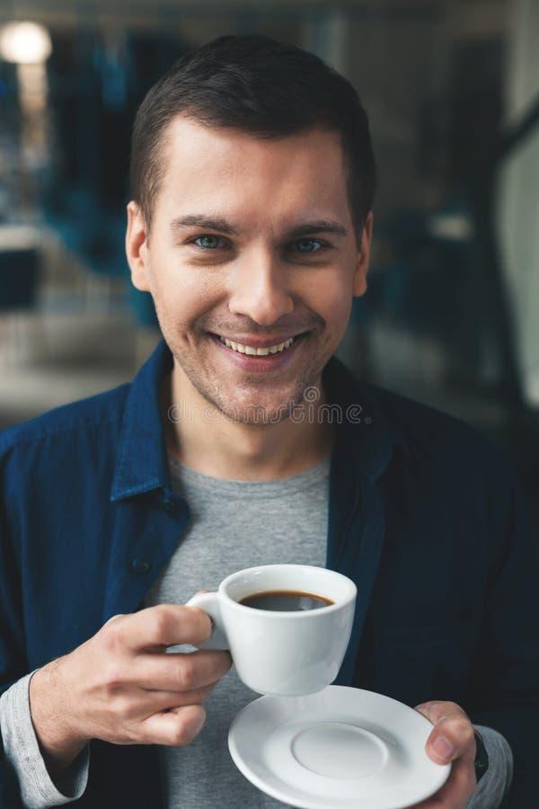 Den attraktiva unga grabben tycker om den varma drinken royaltyfri fotografi
