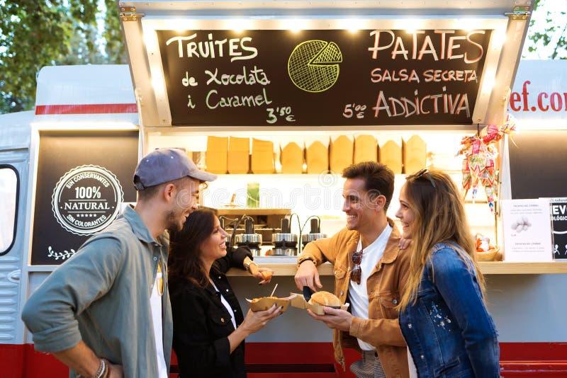 Den attraktiva unga gruppen av vänner som besöker och köper snabbmat äter in, marknaden i gatan arkivfoto