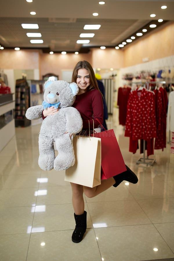 Den attraktiva unga gulliga caucasian kvinnan kramar den flotta nallebjörnen med shoppingpåsar på framdelen för klädlagret Nätt f royaltyfri foto